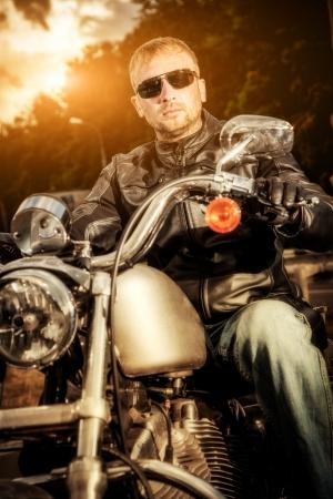 sits: Biker man sits on a bike Stock Photo