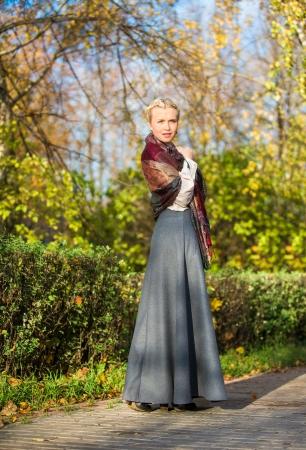 vintage look: Giovane ragazza a piedi in autunno parco cittadino
