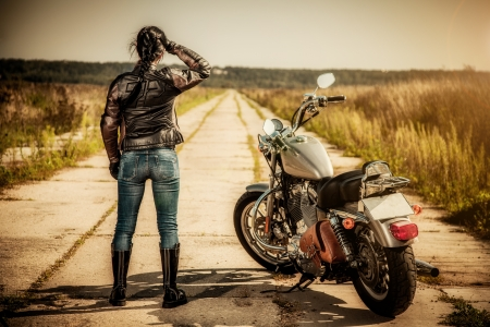 Biker girl stands on the road and looks into the distance
