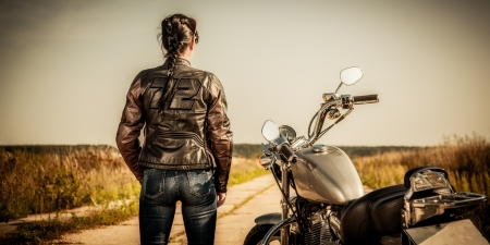 biker girl: Biker girl stands on the road and looks into the distance