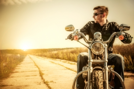 Biker man sits on a bike photo