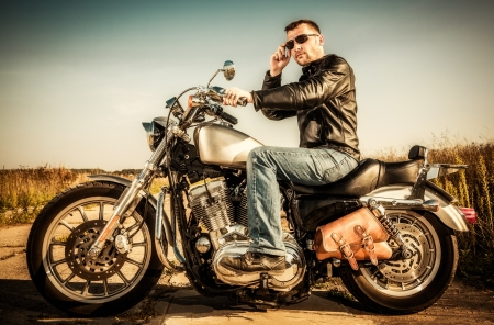 Biker man sits on a bike Stock Photo