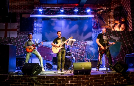 performs: Band performs on stage, rock music