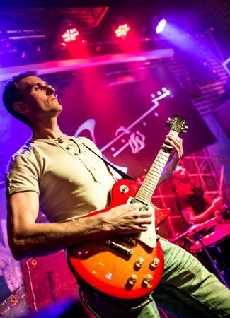 rock band: musician plays a guitar on stage Stock Photo
