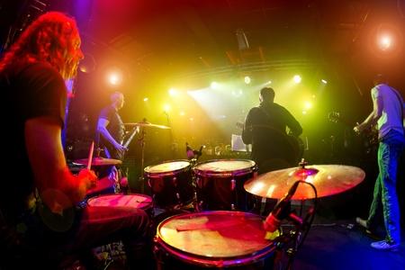 concierto de rock: Las actuaciones de los músicos, el baterista en primer plano