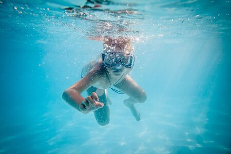 Boy swimming under water in pool photo