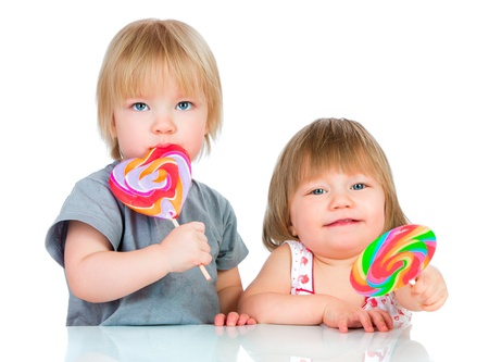 Babies eating a sticky lollipop on white background photo