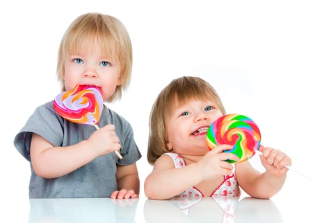 Babies eating a sticky lollipop on white background Stock Photo - 17641909
