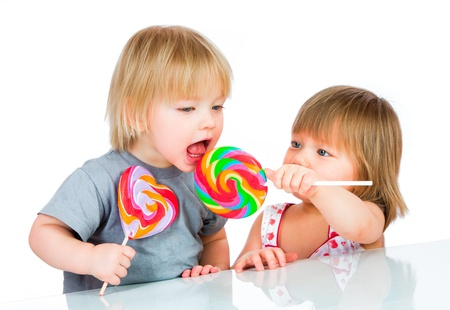 lollipop: Babies eating a sticky lollipop on white background