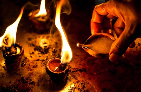 an oil lamp: Burning candles in the Indian temple. Diwali  the festival of lights.