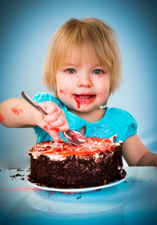 Little baby girl eating cake on a blue background photo
