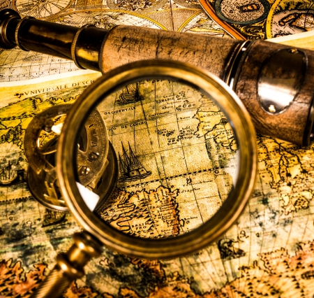 Vintage magnifying glass, compass, telescope lying on an old map. photo