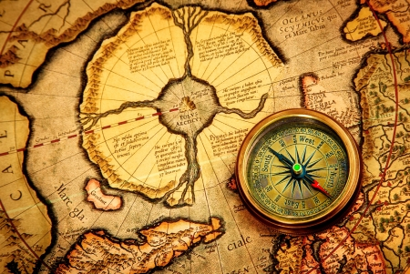 Vintage compass lies on an ancient map of the North Pole (also Hyperborea). Arctic continent on the Gerardus Mercator map of 1595. Stock Photo