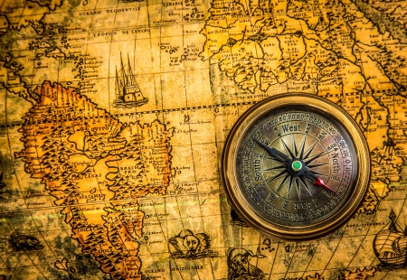 Vintage still life. Vintage compass lies on an ancient world map of 1565. photo
