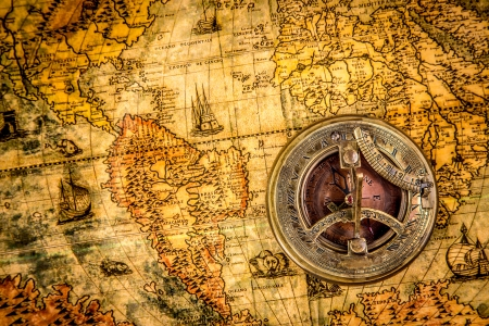 antique map: Vintage still life. Vintage compass lies on an ancient world map of 1565.