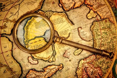 Vintage magnifying glass lies on the ancient map of the North Pole (also Hyperborea). Arctic continent on the Gerardus Mercator map of 1595. photo