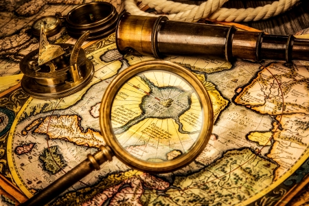 Vintage magnifying glass, compass, telescope lies on the ancient map of the North Pole (also Hyperborea). Arctic continent on the Gerardus Mercator map of 1595. photo