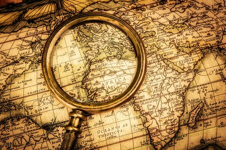 charred: Vintage still life. Vintage magnifying glass lies on an ancient world map