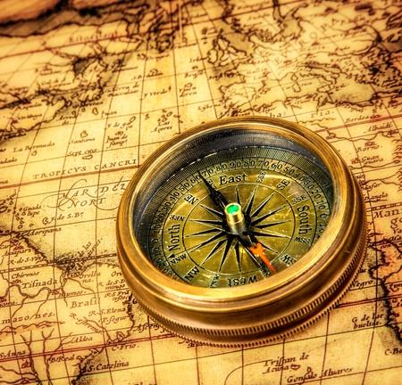 ir�ny: Vintage csendélet. Vintage iránytű fekszik egy ősi világtérképen.