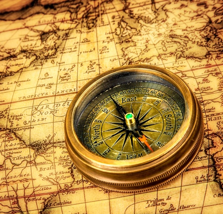 history: Vintage still life. Vintage compass lies on an ancient world map.