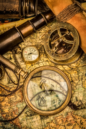 Vintage magnifying glass, compass, telescope and a pocket watch lying on an old map. Stock Photo