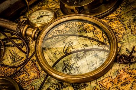 Lente di ingrandimento Vintage, bussola, telescopio e un orologio da tasca che giace su una vecchia mappa. Archivio Fotografico