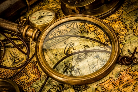 nautical map: Vintage magnifying glass, compass, telescope and a pocket watch lying on an old map.