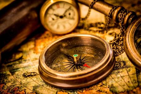 navigation: Vintage still life. Vintage compass lies on an ancient world map.