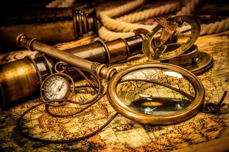 mappa del tesoro: Lente di ingrandimento Vintage, bussola, telescopio e un orologio da tasca che giace su una vecchia mappa.