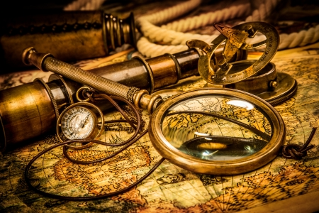 Lupa Vintage, brújula, telescopio y un reloj de bolsillo que miente en un viejo mapa. Foto de archivo