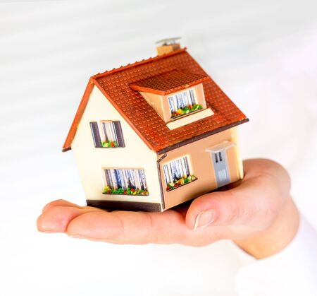 hands holding house: house in human hands on a white background Stock Photo