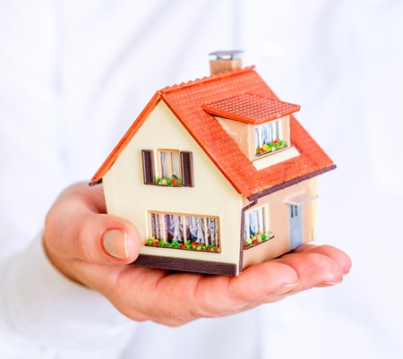 house insurance: house in human hands on a white background Stock Photo