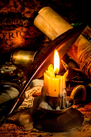 Vintage compass, magnifying glass, quill pen, spyglass lie on an old ancient map with a lit candle photo