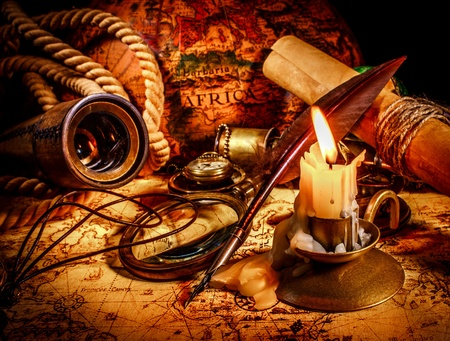 Vintage compass, magnifying glass, quill pen, spyglass lie on an old ancient map with a lit candle. Vintage still life. photo