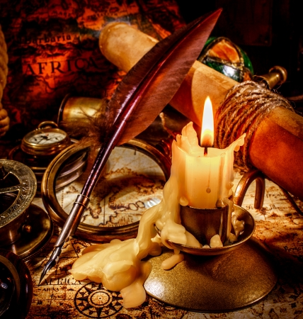 bygone: Vintage compass, magnifying glass, pocket watch, quill pen, spyglass lie on an old ancient map with a lit candle
