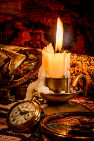Vintage compass, pocket watch lie on an old ancient map with a lit candle photo