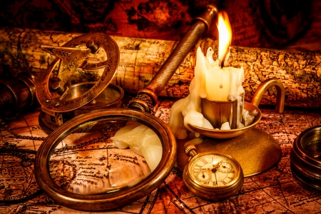 Vintage compass, magnifying glass, spyglass lie on an old ancient map with a lit candle. Vintage still life. photo
