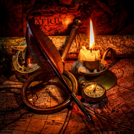 bygone: Vintage compass, magnifying glass, pocket watch, quill pen, spyglass lie on an old ancient map with a lit candle. Vintage still life.
