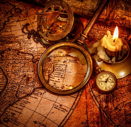 Vintage magnifying glass, pocket watch, compass, spyglass lie on an old ancient map with a lit candle photo