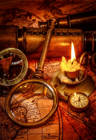Vintage magnifying glass, compass, pocket watch, spyglass lie on an old ancient map with a lit candle photo