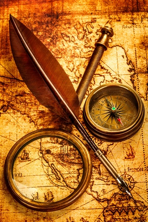 Vintage magnifying glass, compass and goose quill pen lying on an old map. photo