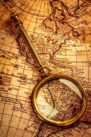 Vintage still life. Vintage magnifying glass lies on an ancient world map photo