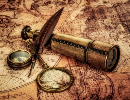 Vintage magnifying glass, compass, goose quill pen and spyglass lying on an old map. photo