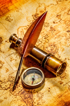spyglass: Vintage compass, goose quill pen, and spyglass lying on an old map.