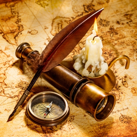 antiquity: Vintage compass, quill pen, spyglass lie on an old ancient map with a lit candle Stock Photo