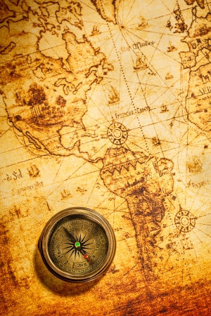 vintage world map: Vintage still life. Vintage compass lies on an ancient world map.