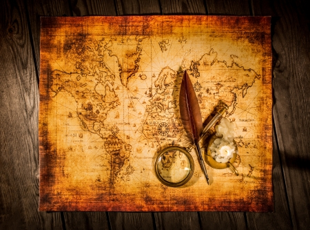 Vintage quill pen and magnifying glass lie on an old ancient map with a lit candle photo