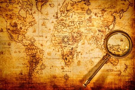 Todav?a de la vendimia la vida. Lente de aumento Vintage yace sobre un antiguo mapa del mundo