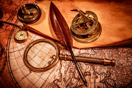 Vintage magnifying glass, compass, goose quill pen and a pocket watch lying on an old map. photo