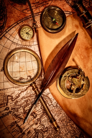 Vintage magnifying glass, compass, goose quill pen, spyglass and a pocket watch lying on an old map. photo